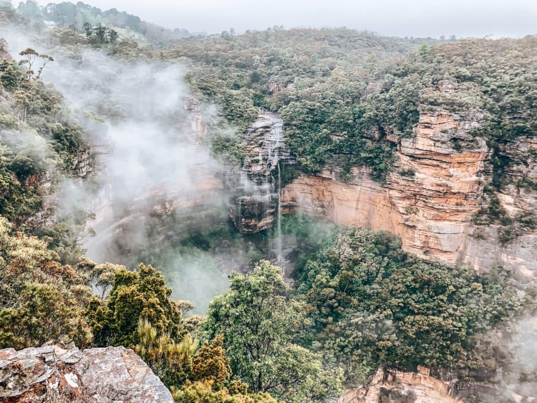 Hiken in de Blue Mountains Als je in Sydney bent dan mag je een trip naar de Blue Mountains echt niet overslaan! Wat een mooie tocht is dit en wij hebben onze ogen uitgekeken. Onderschat de route niet, want hij is best heftig. Wij hadden wel de pech dat het die dag regende en dat zorgde ervoor dat niet alle uitkijkpunten even helder waren. Desondanks was het schitterend. Via steile trappen daal je helemaal af naar beneden waar je zicht hebt op de waterval vanuit onder gezien. Tijdens deze trip stop je het grootste deel van de tijd bij de Blue Mountains, maar er is ook een stop ingelast om de drie gezusters te kunnen spotten.